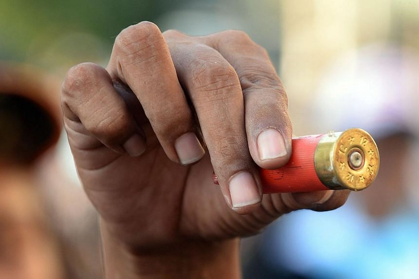 An anti-government protester displays an empty bullet shell allegedly found outside the Government house during a demonstration in Bangkok on December 1, 2013. --PHOTO: AFP