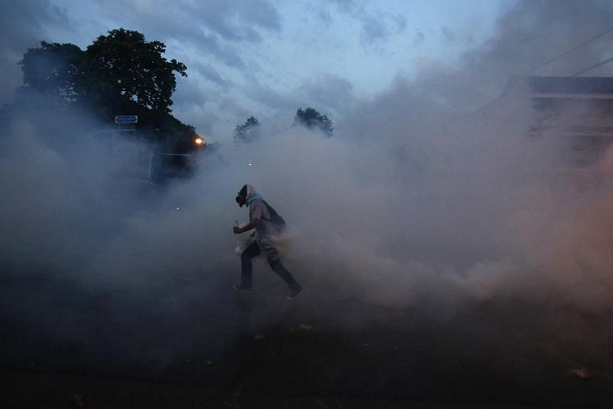 An anti-government protester carries a tear gas canister during clashes with police near the Government house in Bangkok December 1, 2013.--PHOTO: REUTERS