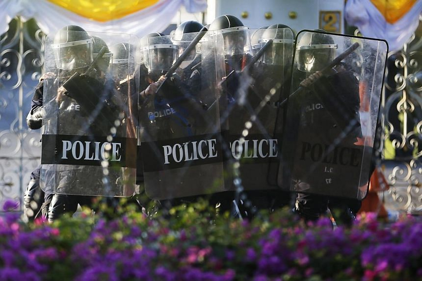 Police move behind their shields as they clash with anti-government protesters near the Government house in Bangkok on December 1, 2013. --PHOTO: REUTERS