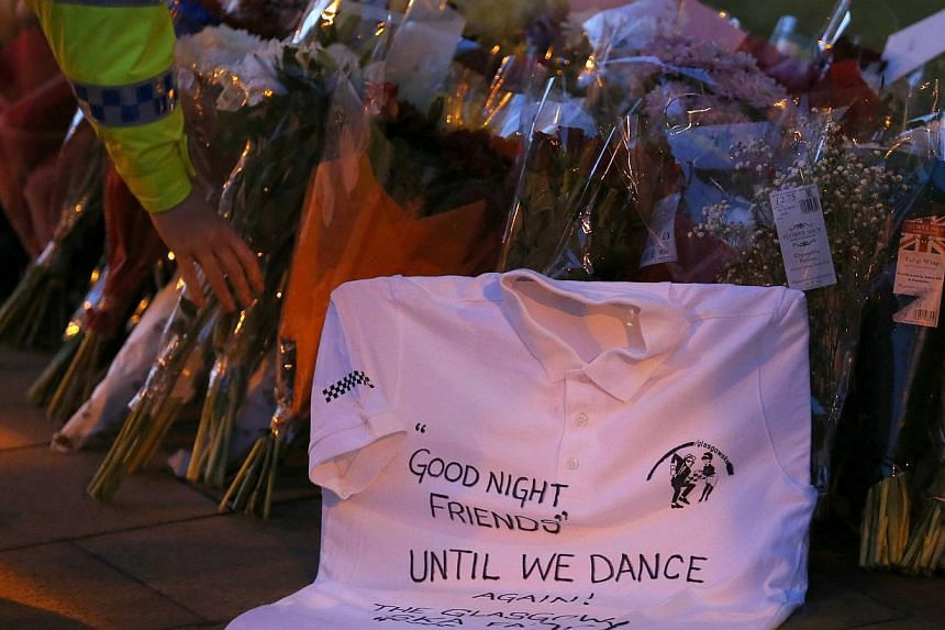 A police officer places a bouquet next to a tribute left near the site of a police helicopter crash on to a pub in central Glasgow, on Dec 1, 2013. Candles were lit on Sunday as Scotland remembered those who were killed when a police helicopter plung