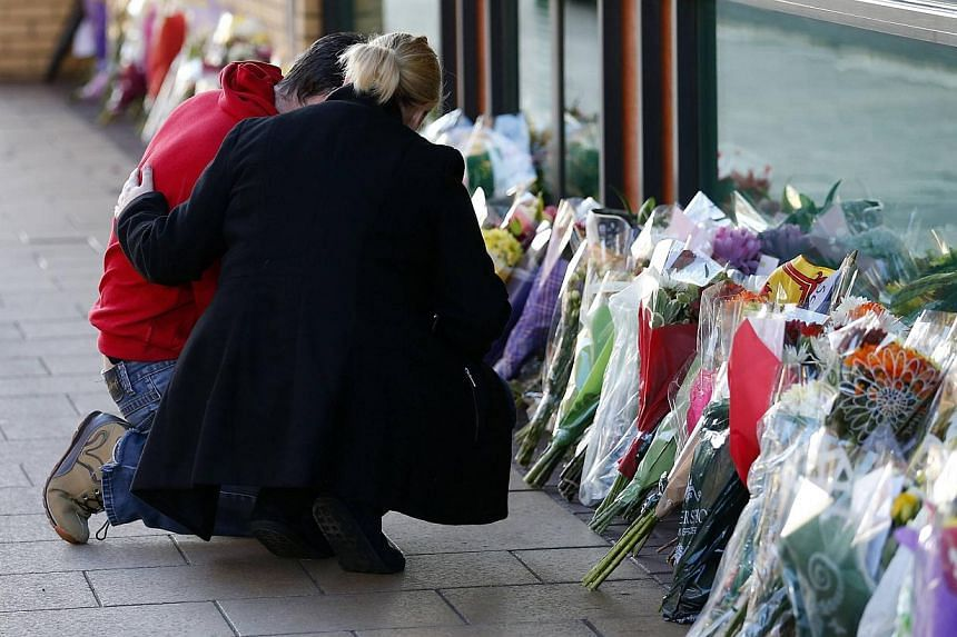 Well wishers comfort each other as they place a bouquet near the site of a police helicopter crash on to a pub in central Glasgow, on Dec 1, 2013. -- PHOTO: REUTERS