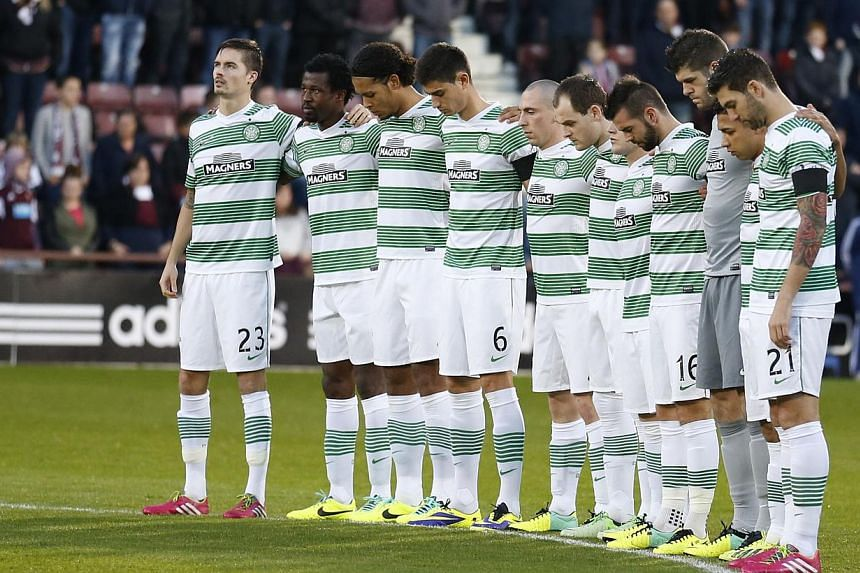 The Celtic team stand for a minute's silence for the victims of the Glasgow helicopter crash, before their Scottish Cup fourth round soccer match against Heart of Midlothian at Tynecastle stadium, Edinburgh, Scotland, on Dec 1, 2013. -- PHOTO: