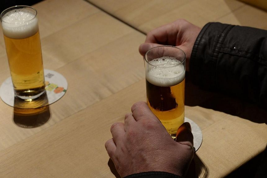 """A guest holding a glass of Cologne """"Koelsch"""" beer on in Cologne, western Germany. German brewers say a five-century-old beer purity law deserves a spot on the Unesco list for """"intangible cultural heritage"""".-- FILE PHOTO: AFP"""