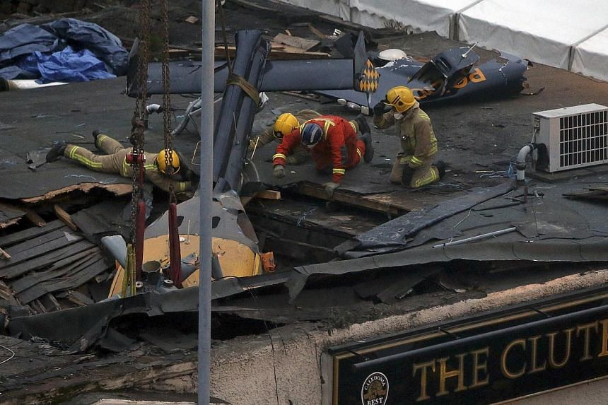 Scottish Fire and Rescue services look on at the helicopter being lifted from the scene, on Monday, Dec 2, 2013, following the helicopter crash at the Clutha Bar in Glasgow, Scotland. -- PHOTO: AP
