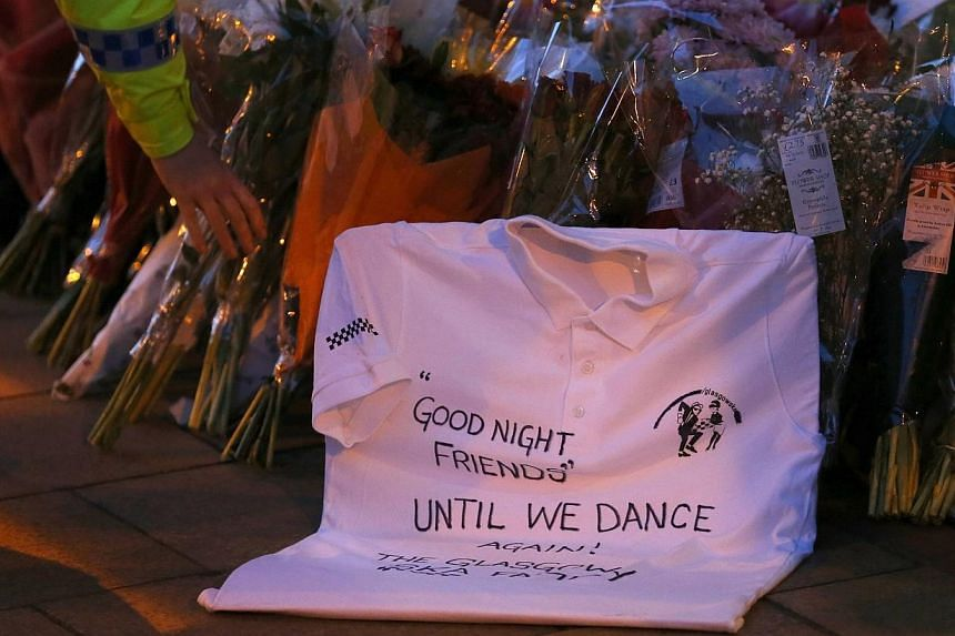 A police officer places a bouquet next to a tribute left near the site of a police helicopter crash on to a pub in central Glasgow, on Dec 1, 2013. -- PHOTO: REUTERS