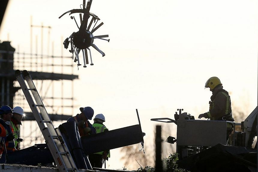 Scottish Fire and Rescue services look on at a section of the helicopter being lifted from the scene, on Sunday, Dec 1, 2013, following the helicopter crash at the Clutha Bar in Glasgow, Scotland. -- PHOTO: AP