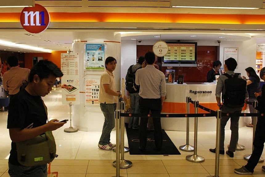 Customers at the M1 shop in Paragon shopping mall, on 17 Jan 2013. Many M1 mobile users were cut off from the Internet for several hours, on Monday morning following a scheduled network upgrade the night before.-- ST FILE PHOTO:DESMOND LU