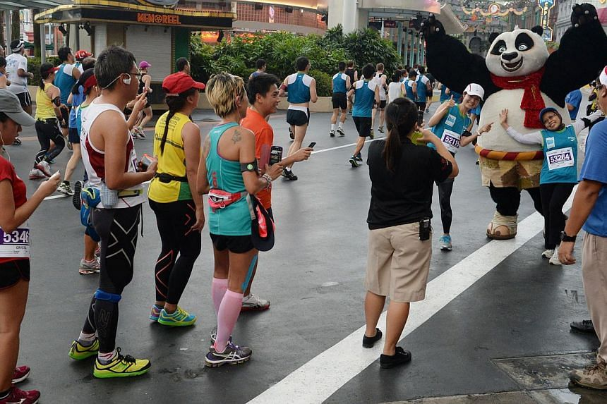 Runners doing the half marathon running through Universal Studios stop to pose for photos with the Kung Fu Panda character  -- ST PHOTO: RAJ NADARAJAN