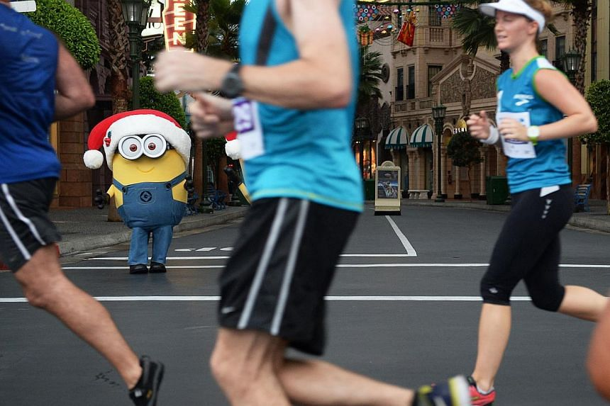 Runners passing a Minion character at Universal Studios on Sunday morning, Dec 1.-- ST PHOTO: RAJ NADARAJAN