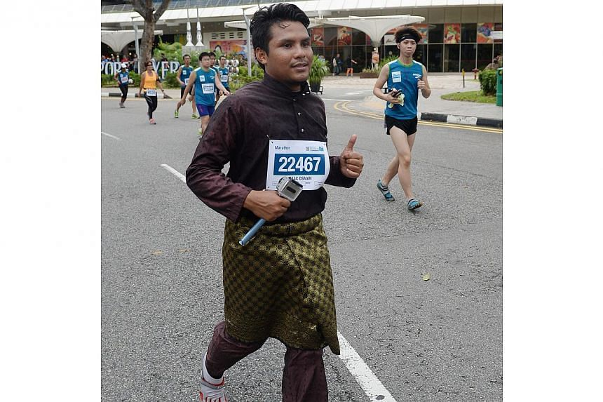 Nur Muhammad Izzat, 25 from Malaysia, running in a traditional Malay outfit at the Standard Chartered Marathon 2013. -- ST PHOTO: RAJ NADARAJAN