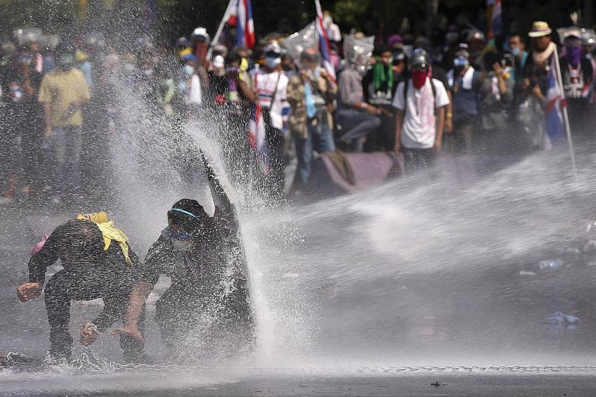 Anti-government protesters are sprayed water cannon by police in Bangkok, Thailand, Monday, Dec 2, 2013. -- PHOTO: AP