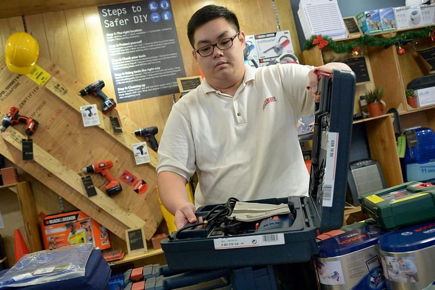 ITE graduate Chow Zhi Hua, 23, a retail assistant at Home-Fix, earns about $1,600. The rising wages appear to be a result of SMEs being more willing to pay more and the manpower crunch. -- ST PHOTO: LIM SIN THAI