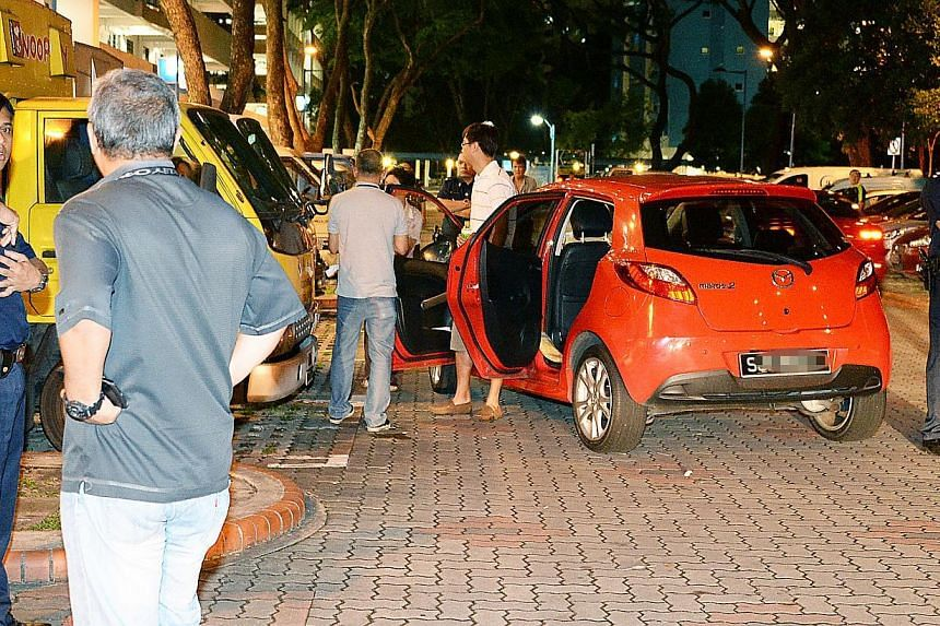 Police officers carrying out investigations at the carpark at Block 57 on Sunday. The victim was forced to drive her car there after being robbed at another open-air carpark nearby.