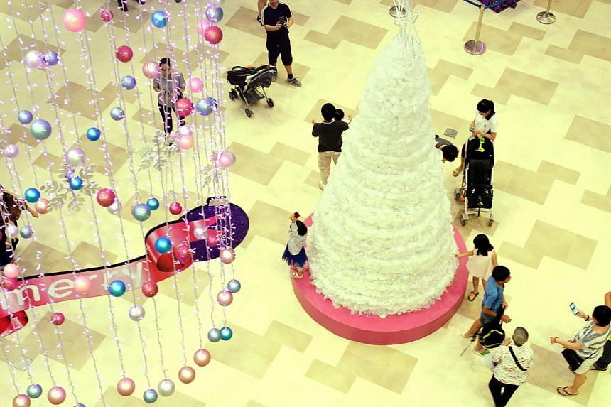People enjoy taking photos of the newly opened Bedok Mall's Christmas tree, a one-of-a-kind, environmentally friendly Christmas tree crafted from some 2,000 recycled plastic milk bottles.-- ST PHOTO: AZIZ HUSSIN