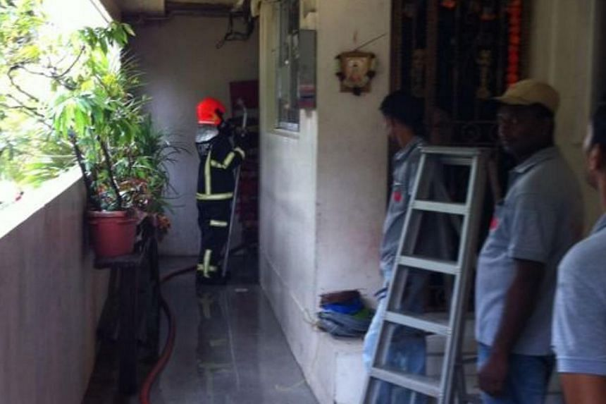 Singapore Civil Defence Force (SCDF) firefighters were called in at 7.20am on Tuesday after a fire broke out at a flat in Block 123 Pending Road.-- ST PHOTO:DESMOND FOO