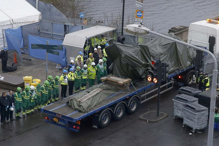 Rescue workers watch as the wreckage of a police helicopter is driven away in central Glasgow, Scotland on Dec 2, 2013. The search and recovery operation carried out after a police helicopter smashed through the roof of a Glasgow pub concluded Monday