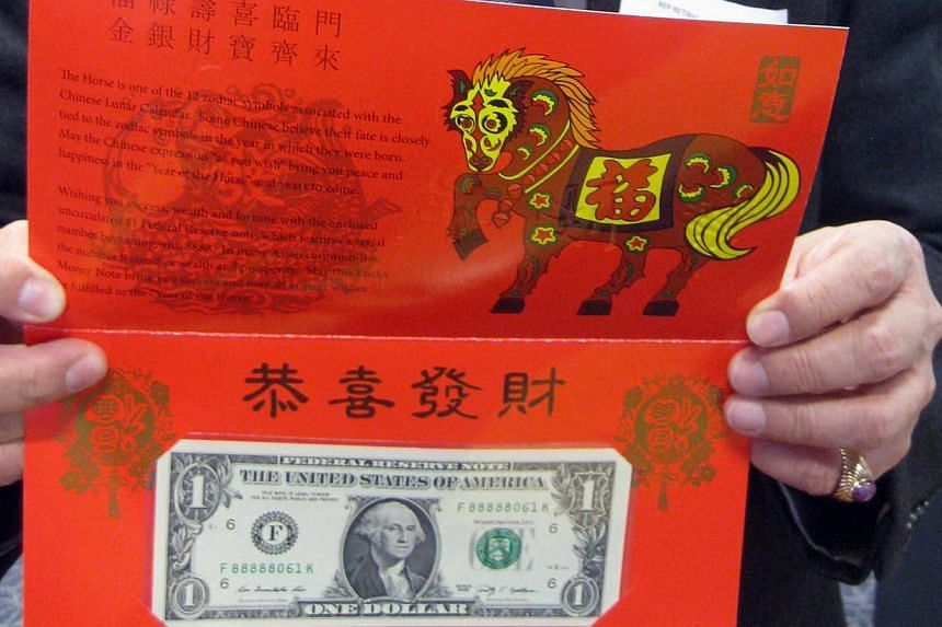 """The """"Year of the Horse"""" one dollar bill is displayed for the media at the Bureau of Engraving and Printing (BEP) in Washington, DC, on Dec 3, 2013. The United States (US) Treasury is selling red """"hong bao"""" envelopes with """"lucky"""" dollars bearing auspi"""