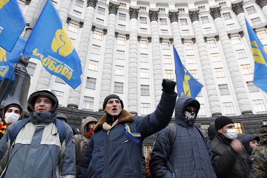 People gather in front of the Ukrainian cabinet of ministers building during a rally to support EU integration in Kiev on Wednesday, Dec 4, 2013.Ukrainian Prime Minister Mykola Azarov on Wednesday called on the opposition to stop escalating ten