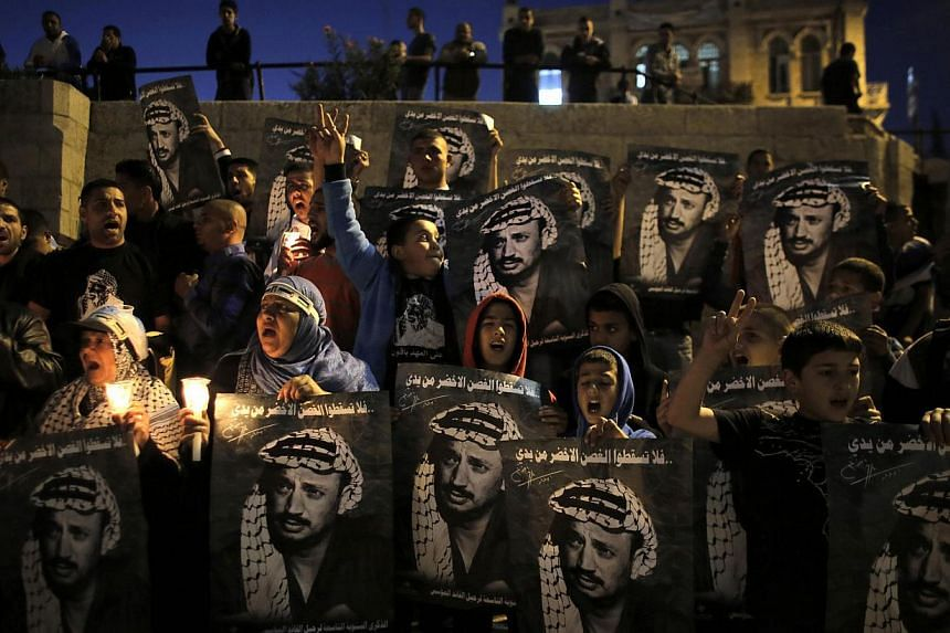 Palestinians hold posters depicting late Palestinian leader Yasser Arafat during a rally marking the 9th anniversary of his death near Damascus Gate in Jerusalem's Old City on Nov 11, 2013.The widow of late Arafat said on Wednesday, Dec 4, 2013