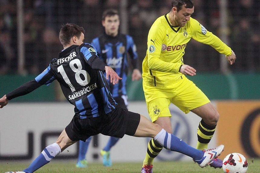 Dortmund's striker Julian Schieber (Right) and Saarbruecken's Nils Fischer vie for the ball during the 3rd round German Cup (DFB - Pokal) football match. Depleted Dortmund shrugged off the absence of more than half a dozen starting players to ea