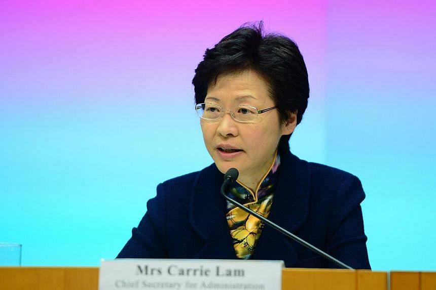 Hong Kong Chief Secretary Carrie Lam answers questions in a press conference on Dec 4, 2013 about elections of the city's chief executive in 2017 and the legislative council in 2016. -- PHOTO: XINHUA