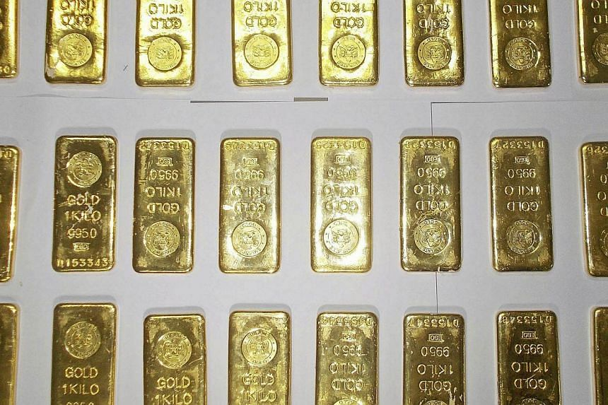 Seized gold bars are kept on displayed by custom officers at the international airport in Kolkata in this Nov 19, 2013 file photo.Indian gold smugglers are adopting the methods of drug couriers to sidestep a government crackdown on imports of t
