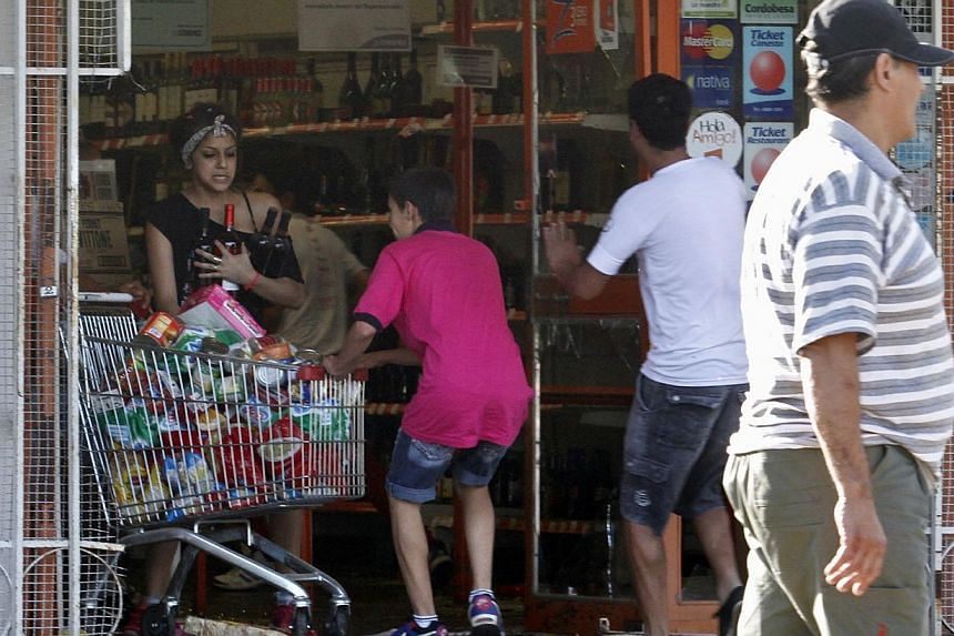 Looters leave a supermarket in Cordoba, Argentina, on Dec 3, 2013. At least one person died when people robbed stores in the central Argentine province of Cordoba after police demanding pay raises refused to leave their barracks, a doctor said o