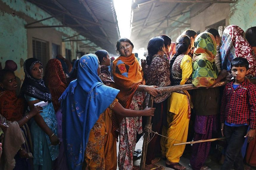 Voters line up in a queue outside a polling booth to cast their vote during the state assembly election in Delhi, on Dec 4, 2013. A new Indian political party rooted in an anti-corruption movement that swept the country in 2011 faced its first e