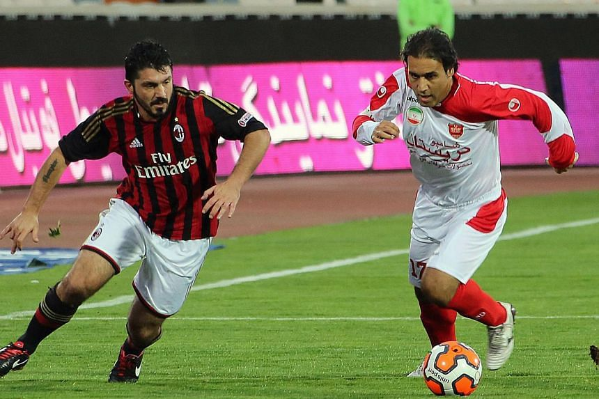Former AC. Milan player Gennaro Gattuso (L) defends against former Persepolis player Mehdi Mahdavikia (R) during an exhibition soccer match at the Azadi stadium in Tehran on November 28, 2013. -- FILE PHOTO: AFP