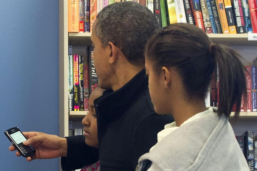 US President Barack Obama reads from his Blackberry cellphone alongside his daughters Sasha (left) and Malia (right) during a shopping trip in Arlington, Virginia, Nov 24, 2012. Mr Obama admitted on Wednesday he was not allowed to have an iPhone