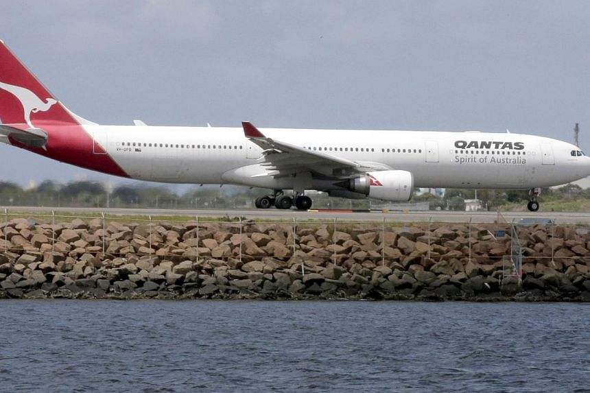 "Australian carrier Qantas said it would axe 1,000 jobs and anticipates ""immense"" challenges ahead in a shock profit warning on Thursday, flagging a half-year loss of up to A$300 million (S$339 million). -- FILE PHOTO: AP"