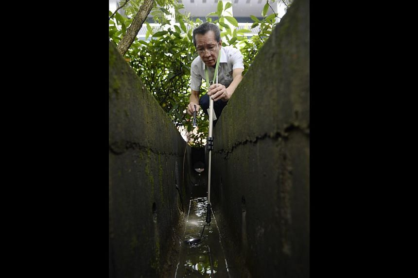 Environmental health officer Lim Soon Nguan checking a drain in the Somerset area. The source of the epidemic in Orchard Road was the Orchard Gateway construction site, where 54 dengue cases were reported.-- ST PHOTOS: MUGILAN RAJASEGERAN
