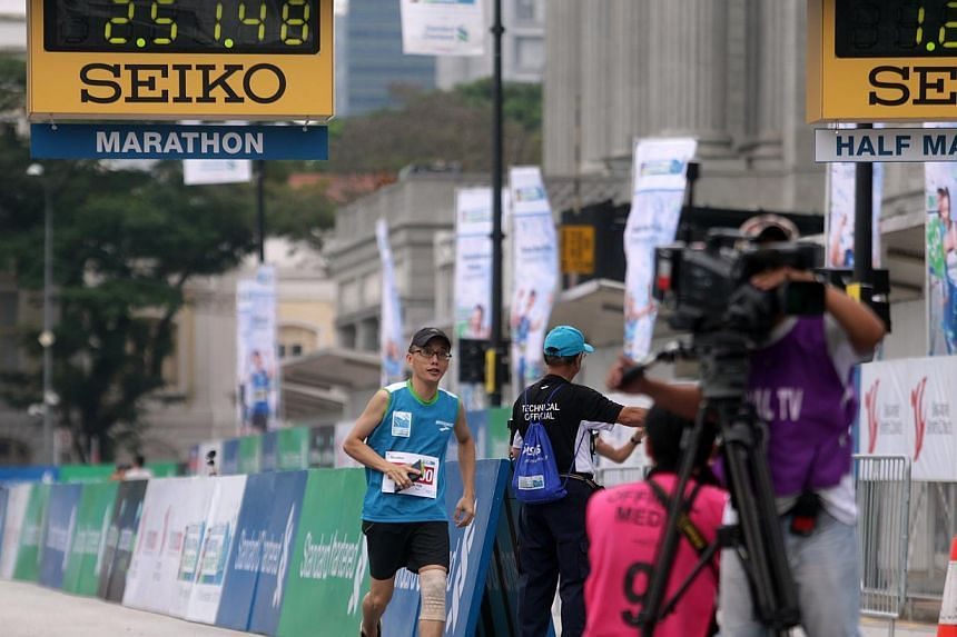 Mr Tam crossing the finishing line after taking a short cut on Sunday.-- ST PHOTOS: KEVIN LIM, ASHLEIGH SIM