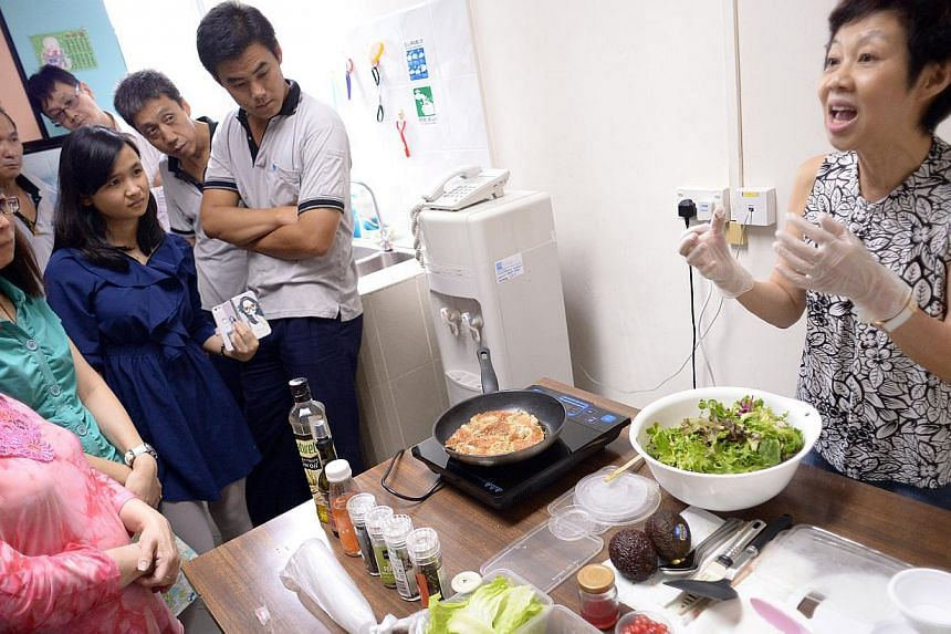 Nutrition consultant Yam Yoke Yin showing Asia Polyurethane staff the way to prepare healthy dishes as part of the firm's health programme.