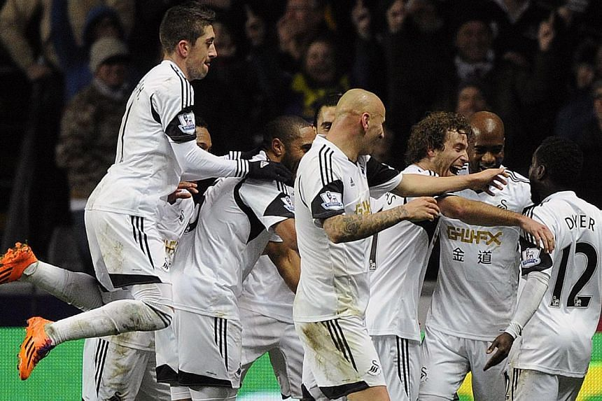 Swansea City's Nathan Dyer (right) celebrates scoring a goal against Newcastle United with his teammates during their English Premier League soccer match at the Liberty Stadium in Swansea, Wales, on Dec 4, 2013. Swansea City brought Newcastle United'
