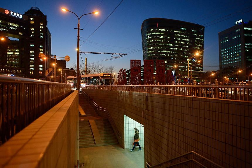 A pedestrian passes beneath a road junction in Beijing on Thursday, Dec 5, 2013. Beijing is the second-most expensive city in Asia for expatriates, jumping up the ranking from fifth place last year, while Tokyo still tops the list despite a shar