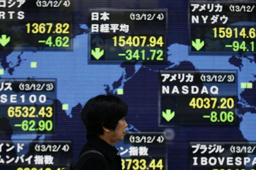 A woman walks past an electronic board displaying Japan's Nikkei average (top, centre) and various countries' stock price indices, outside a brokerage in Tokyo on Wednesday, Dec 4, 2013.Tokyo will announce a spending package worth almost 5.5 tr