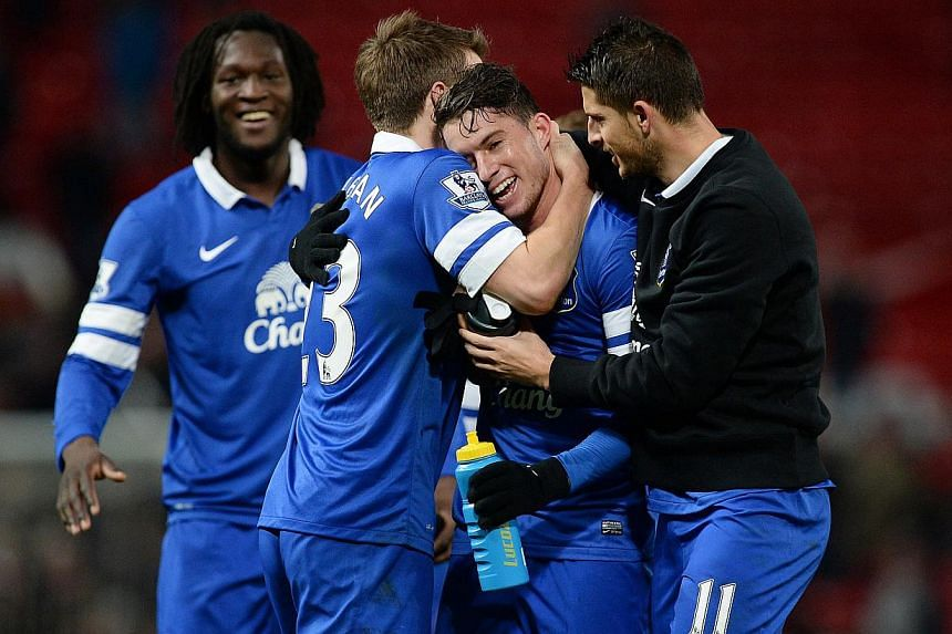 Everton's Bryan Oviedo (second right) celebrates with teammates after their English Premier League soccer match against Manchester United at Old Trafford, northern England, Dec 4, 2013. Oviedo scored the only goal as Everton recorded a shock 1-0 win
