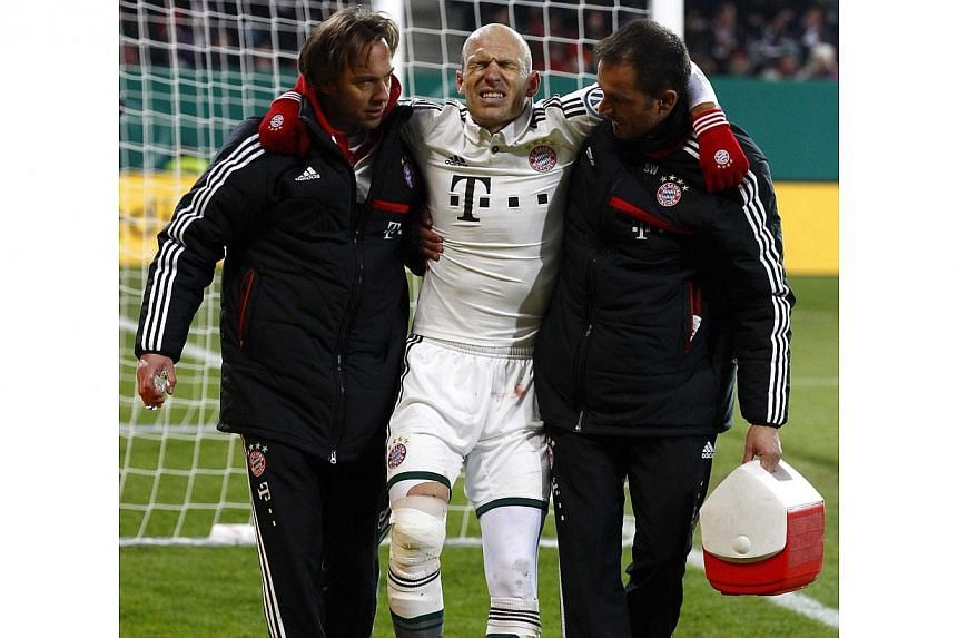 Bayern Munich's Arjen Robben leaves injured the pitch during their third round German soccer cup (DFB-Pokal) match against Augsburg in Augsburg, on Dec 4, 2013. Dutch star Arjen Robben is out for six weeks after suffering a painful knee injury in Bay