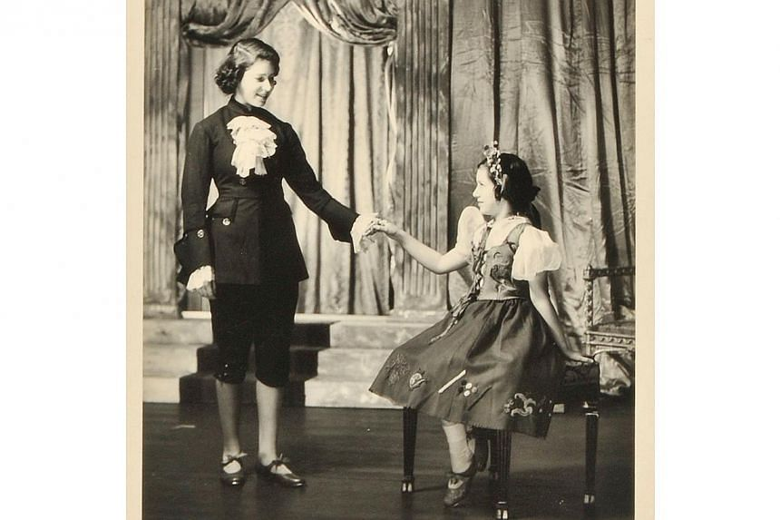 A handout reproduction picture released by Dominic Winter Auctioneers on Dec 4, 2013, shows a signed photograph of the then Princess Elizabeth (left), now Queen Elizabeth II, Princess Margaret (right) performing in the play Cindarella at the Royal Sc