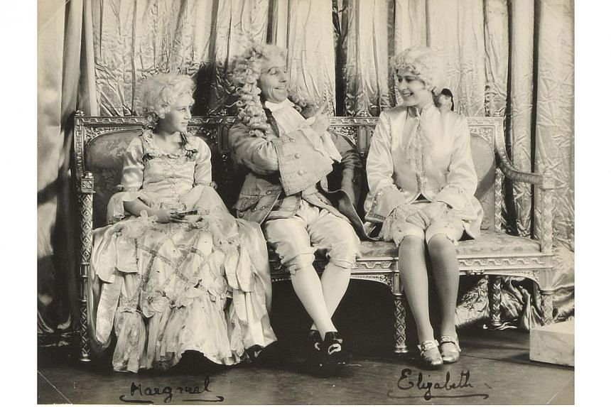 A handout reproduction picture released by Dominic Winter Auctioneers on Dec 4, 2013, shows a signed photograph of the then Princess Elizabeth (right), now Queen Elizabeth II, Princess Margaret (left) on the set of the play Cinderella in Windsor in 1