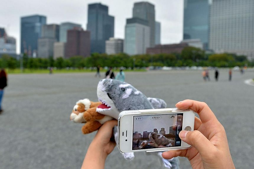 Tour operator Sonoe Azuma takes a picture of a stuffed toy during a visit to a tourist area in Tokyo on Oct 4, 2013. A Japanese travel agency is offering package tours for stuffed animals. -- FILE PHOTO: AFP
