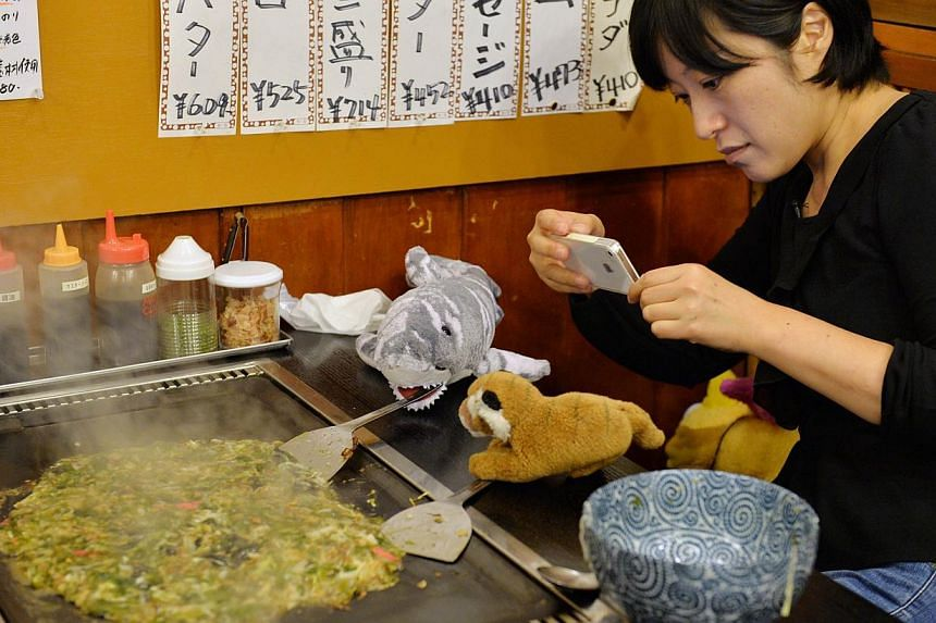 Tour operator Sonoe Azuma takes a picture of stuffed toys during a visit to a restaurant in Tokyo on Oct 4, 2013.  A Japanese travel agency is offering package tours for stuffed animals. -- FILE PHOTO: AFP