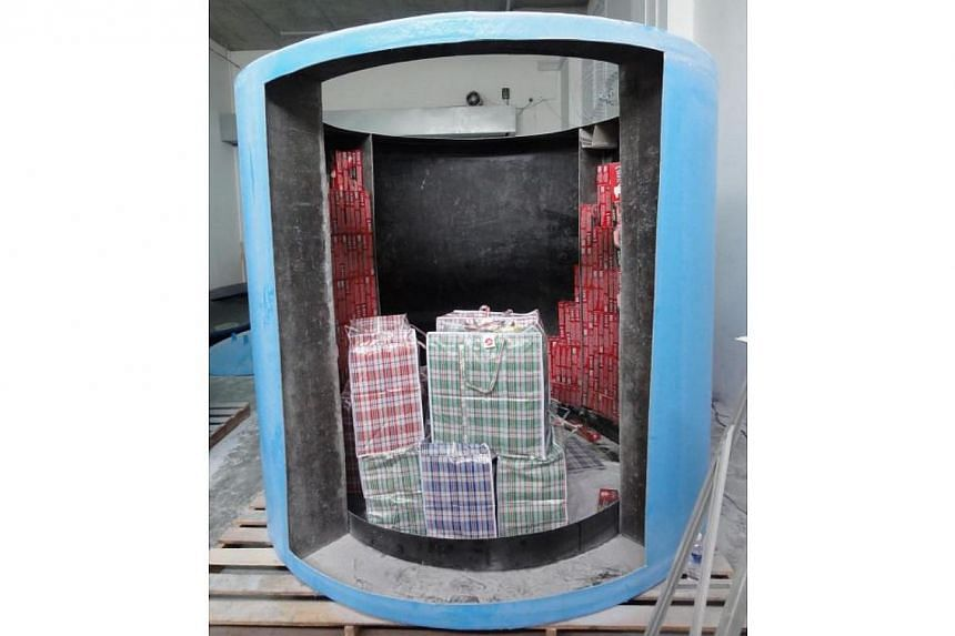 The four men who were retrieving contraband cigarettes from the four fibre tanks and packing them into bags on Dec 3, 2013, were arrested by SingaporeCustoms officers. A total of 17,393 cartons and eight packets of duty-unpaid cigarettes were r