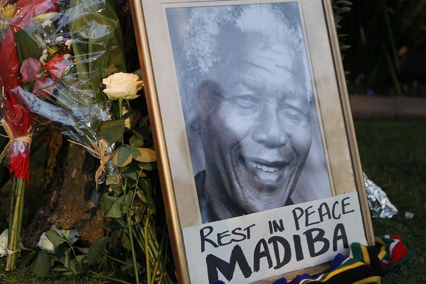 A framed portrait of former president Nelson Mandela and flowers are placed outside Mr Mandela's Johannesburg home on Friday, Dec 6, 2013, after the freedom fighter passed away on Thursday, Dec 5, 2013, after a long illness.Chinese mourned Mr M