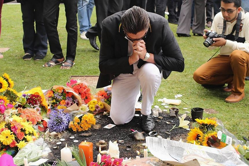 A man pays his respects outside the residence of former South African president Nelson Mandela in Johannesburg on Friday, Dec 6, 2013. Preparations began on Friday for the state funeral of Mr Mandela, as the world mourned the peace icon's passin