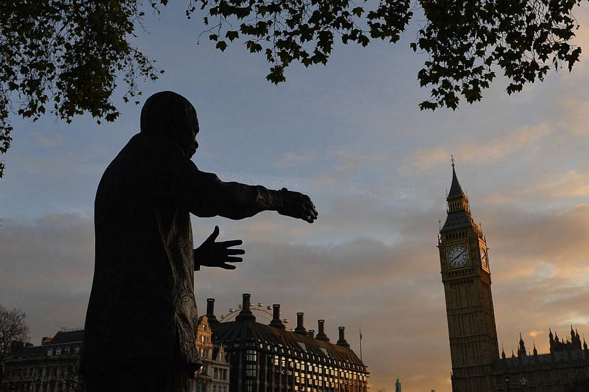A statue of former South African president Nelson Mandela is seen with the Big Ben clock and the Houses of Parliament in the background at dawn in London on Friday, Dec 6, 2013. MrMandela's long walk from apartheid prisoner to South African pre