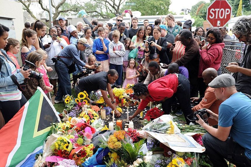 People light candles on Friday, Dec 6, 2013, outside the house of former South African president Nelson Mandela in Johannesburg following his death. MrMandela's grandson expressed gratitude for the global outpouring of support since the 95-year