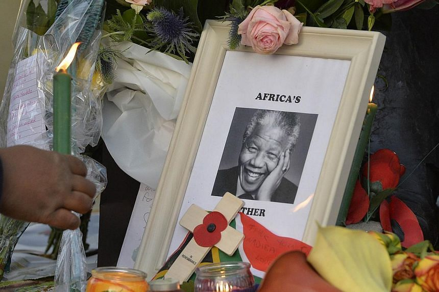 A woman places a candle next to tributes at a statue of former South African president Nelson Mandela in Parliament Square in London on Friday, Dec 6, 2013.Israeli President Shimon Peres and Prime Minister Benjamin Netanyahu paid tribute to Mr