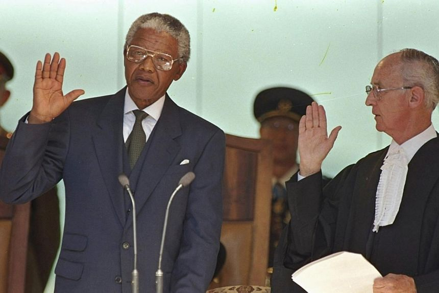 """Mr Mandela taking his oath to become South Africa's first black president in May 10, 1994. In his speech, he said: """"Never, never and never again shall it be that this beautiful land will again experience the oppression of one by another and suffer th"""